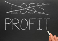 Crossing out loss and writing profit on a blackboard.